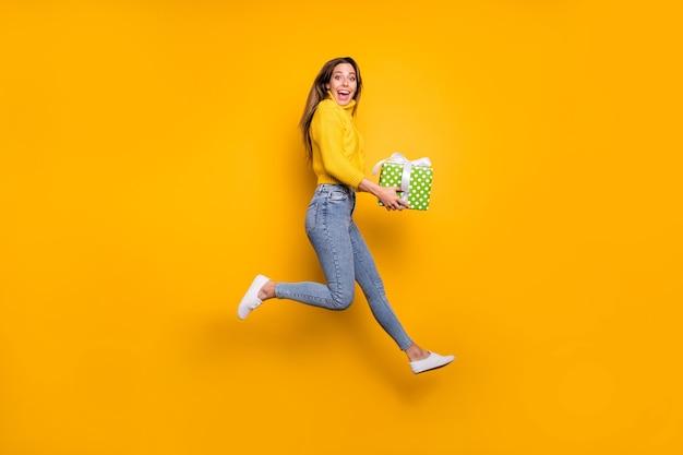 Фото сбоку в полный рост изумленной сумасшедшей фанки-девушки, похожей на праздничные распродажи, подарочная коробка с зеленым пунктиром приносит парню прыгать, бегать, носить повседневную одежду, изолированную на стене желтого цвета