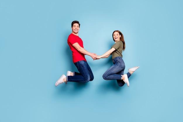 매력적인 두 사람이 여자 남자의 전체 길이 프로필 측면 사진 휴식 휴식 점프 주말을 즐기십시오 파란색 배경 위에 절연 녹색 티셔츠 데님 청바지 스니커즈 착용