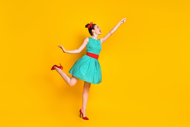 Фото сбоку в полный рост веселой девушки, держащей руку, одетую в бирюзовый наряд, изолированную на ярком цветном фоне