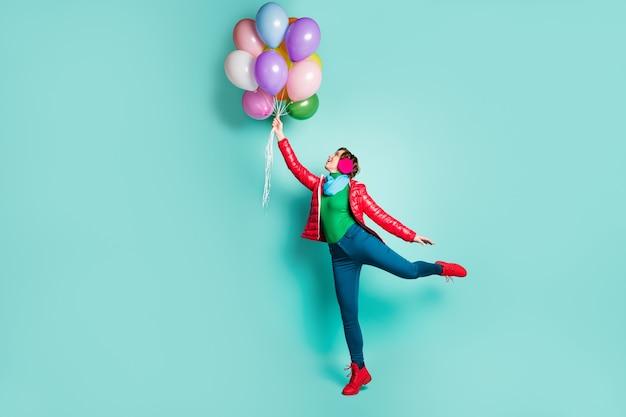 쾌활한 긍정적 인 소녀의 전체 길이 프로필 측면 사진은 많은 헬륨 풍선을 날리는 가을 휴가 캐치 바람을 즐길 수 청록색 벽 위에 절연 분홍색 녹색 점퍼 신발을 착용