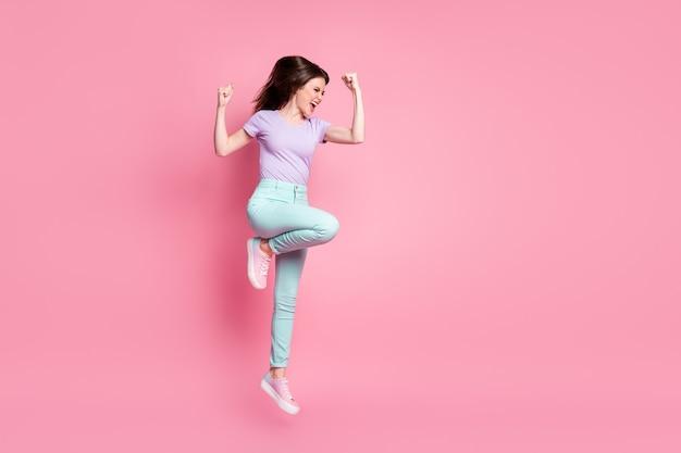 Фото сбоку в полный рост сумасшедшей экстатической девушки в прыжке, поднять кулаки, кричать, праздновать удачную победу, носить бирюзовые фиолетовые брюки, кроссовки, изолированные на пастельном цветном фоне