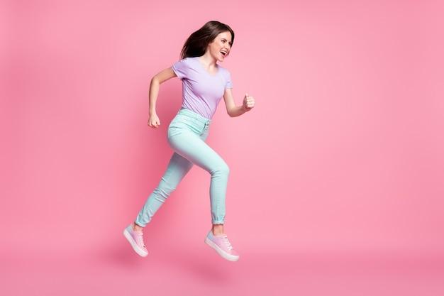 Фото сбоку в полный рост сумасшедшей девушки, слышащей невероятные скидки, прыжки, беги, быстрые, copyspace, фиолетовая одежда, кеды, изолированные на розовом цветном фоне
