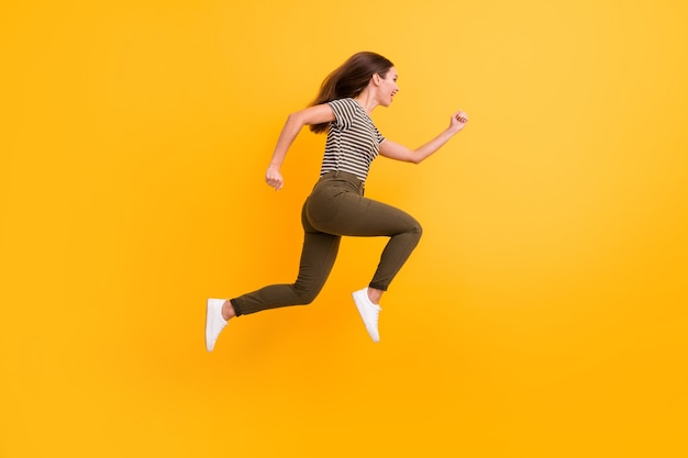 Фото сбоку в полный рост забавной сумасшедшей девушки в прыжке и беге в красивой одежде, изолированной на стене цвета блеска