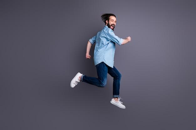 Фото сбоку в полный рост смешного сумасшедшего парня в прыжке, бега после черной пятницы, мечтательная выгодная одежда в повседневном стиле, изолированном над серой стеной