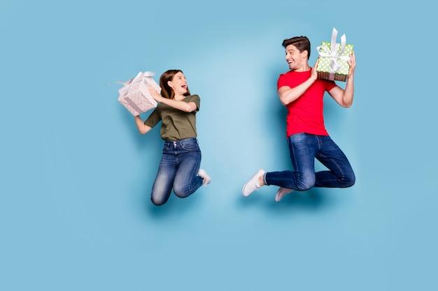 Фото сбоку в полный рост смешных сумасшедших двух человек, супруга, романтическое свидание 14 февраля, получите подарочные коробки, радуйтесь, прыгайте, джинсовые джинсы, красная зеленая футболка, изолированные на синем фоне