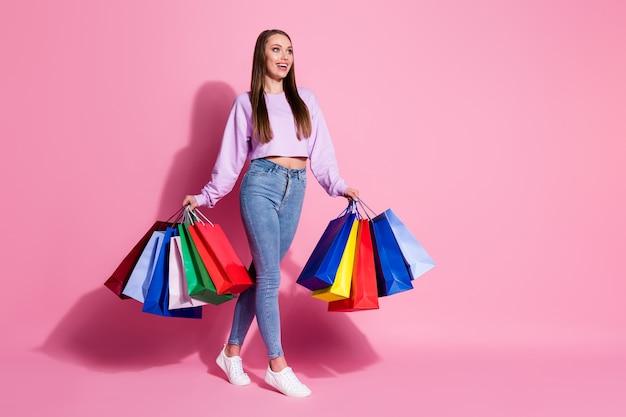 ポジティブで陽気な女の子のフルレングスのプロフィールサイド写真は、パステルカラーの背景の上に分離されたショッピングウェアライラックスタイルのスタイリッシュなトレンディなジャンパーデニムジーンズを楽しむ多くのバッグを保持します
