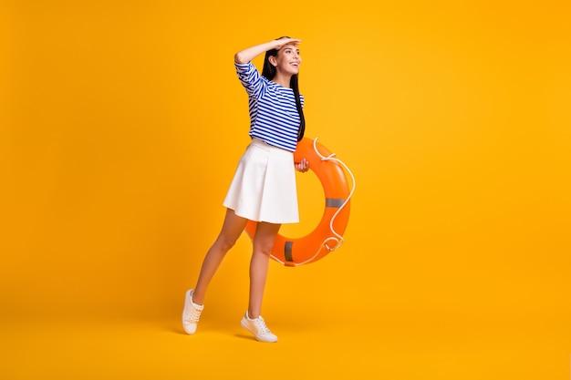 ポジティブな女の子のフルレングスのプロフィールサイド写真は、手の顔を見てコピースペースを参照してください水海を参照してくださいゴム製の救命浮き輪は白いスタイルの服を着て孤立した明るい輝きの色の背景