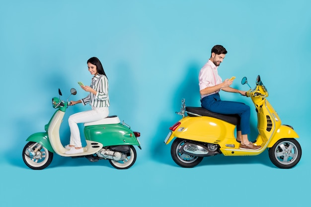 Full length profile side photo of positive two people bikers driver drive yellow green choppers use cellphone search gps location wear trousers shirt isolated blue color wall