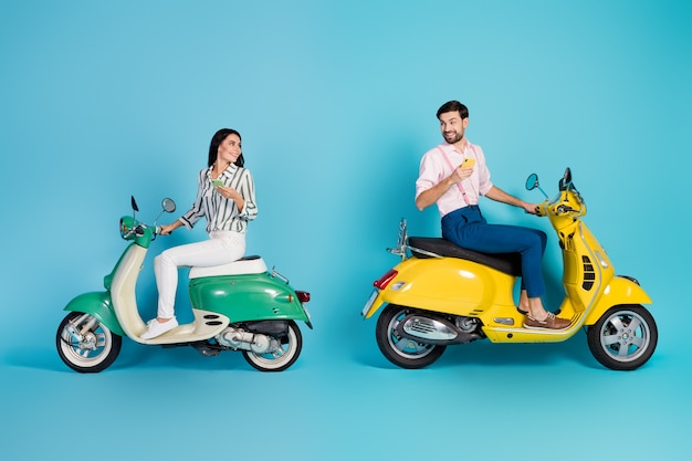 전체 길이 프로필 측면 사진 긍정적 인 두 사람 아내 남편 앉아 노란색 모터 자전거 사용 스마트 폰 찾기 모험 여행 위치 착용 formalwear 셔츠 바지 절연 파란색 벽