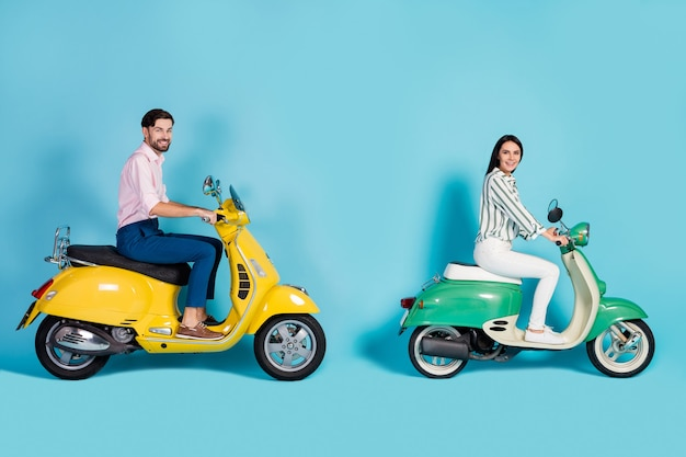 Full length profile side photo positive wife husband bikers drive yellow green motorcycle enjoy street trip wear white striped shirt pink pants trousers isolated blue color wall