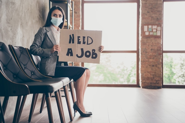 Full length profile side photo of scared girl marketer agent sit chair have job interview feel worry hold card board text wear blazer jacket high-heels medical mask in workplace workstation