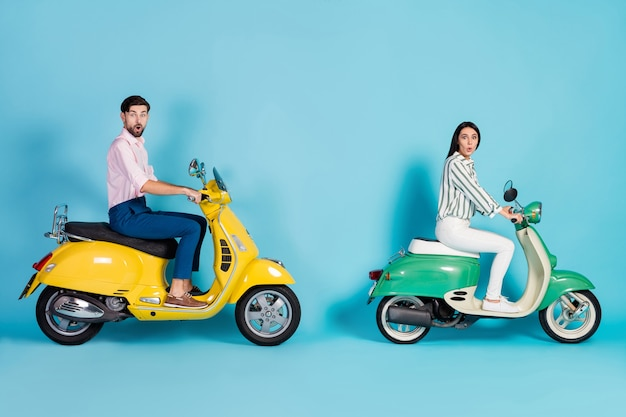 Full length profile side photo wife husband drive yellow green choppers impressed fast speed trip adventure scream wow omg wear striped shirt pants trousers isolated blue color wall