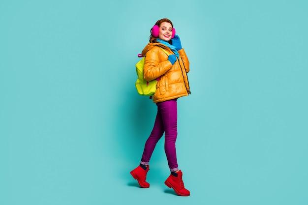 긍정적 인 쾌활한 감정의 전체 길이 프로필 측면 초상화 여자 이동 산책 코스 노란색 보라색 파란색 녹색 점퍼 빨간색 유행 부츠를 착용하십시오.