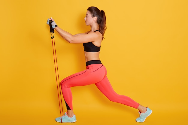 Full length profile view of young brunette woman wearing stylish exercise clothing and stretching in leg lunge position with expander, posing isolated on yellow. sport concept.