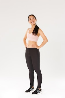 Full length of proud and happy female athlete in sportswear looking happy and accomplished, fitness girl gaining her sports goal, looking delighted, workout in gym