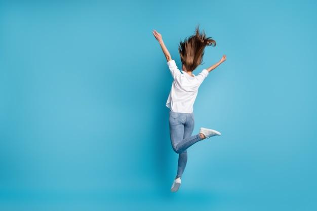 Полная длина сзади сзади фото женщины прыгать высоко поднимать руки носить белую рубашку джинсовые туфли, изолированные на синем цветном фоне