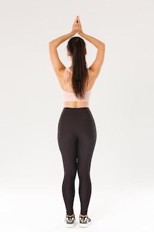 활성 착용 연습 요가, 혼자 운동에 슬림 갈색 머리 아시아 여자의 전체 길이 후면보기, 명상, 아사나에서 머리 위로 푹 손으로 서.