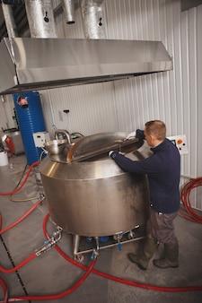 Снимок в полный рост рабочего, заглядывающего в пивной резервуар на пивоварне