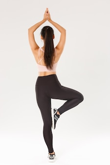 Full length rear view of slim brunette asian girl in active wear practice yoga, workout alone, standing with hands clasped over head in asana, meditating.