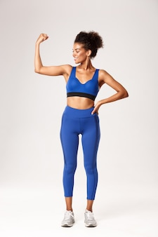 Full length of satisfied smiling african-american woman with perfect body, wearing sportswear, flex