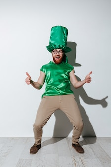 Full length of screaming man in green costume