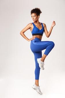 Full length of serious african-american sportswoman in blue leggings and sports bra, raising leg up