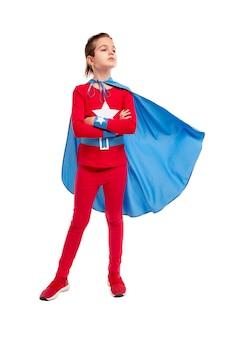 腕を組んで岬を振って、白に立って目をそらしているスーパーヒーローの衣装を着た全身の真面目な少年