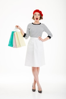 Full length shocked ginger woman with arm on hip and packages looking at the camera over grey