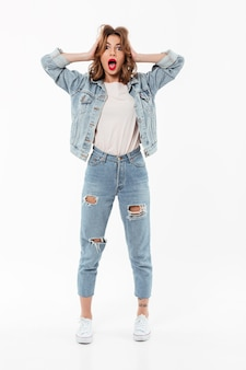 Full length shocked woman in denim clothes holding her head  over white wall
