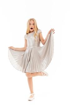 Full length shocked young blonde girl in dress posing on white