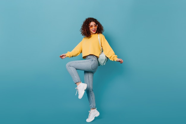 Full-length shot of active girl in skinny jeans and yellow sweatshirt raising her leg on blue space.