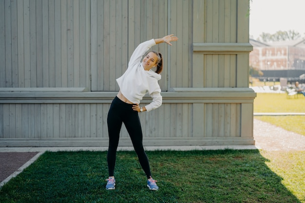 Full length shot of active sportswoman does exercises outdoors stetches body leans at different sides wears sweatshirt trousers and trainers listens music in earphones has fir body smiles happily