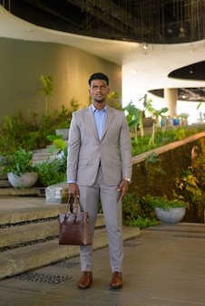 Full length shot of african businessman holding bag and looking at front