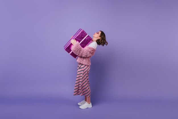 Scatto a figura intera di una fantastica ragazza di compleanno in scarpe da ginnastica bianche che tiene il suo regalo. modello femminile riccio in giacca rosa in posa con regalo.