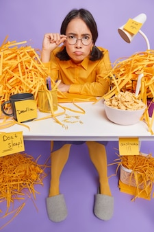 Full length shot of attentive asian female student looks through round glasses focused listens information gets task poses at white desk with cut paper around eats cereals for breakfast