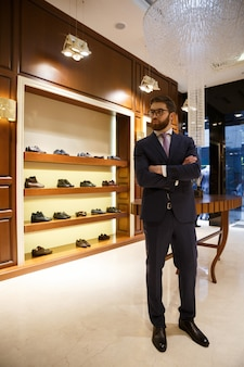 Full-length shot of bearded man in suit and glasses standing in wardrobe and looking away
