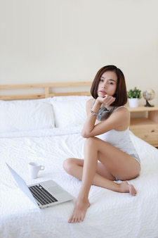 Full length shot of beautiful adult asian woman in white dress sitting on bed.