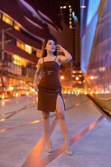 Full length shot of beautiful asian woman outdoors in bangkok, thailand at night