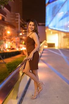 Full length shot of beautiful asian woman outdoors in bangkok, thailand at night Premium Photo