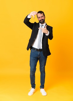 Full-length shot of business man over isolated yellow background focusing face, framing symbol