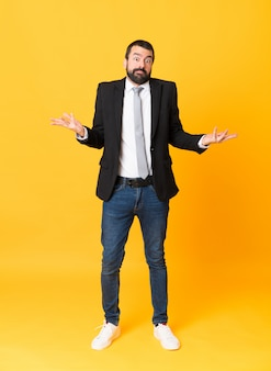 Full-length shot of business man over isolated yellow background making doubts gesture