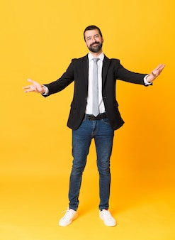 Full-length shot of business man over isolated yellow background presenting and inviting to come with hand