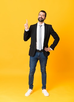 Full-length shot of business man over isolated yellow background showing and lifting a finger in sign of the best