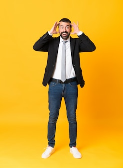 Full-length shot of business man over isolated yellow background with surprise expression