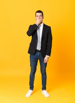 Full-length shot of business man over isolated yellow covering mouth with hands