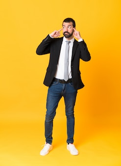 Full-length shot of business man over isolated yellow having doubts and thinking