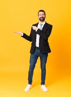 Full-length shot of business man over isolated yellow holding copyspace imaginary on the palm to insert an ad
