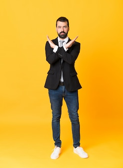 Full-length shot of business man over isolated yellow making no gesture