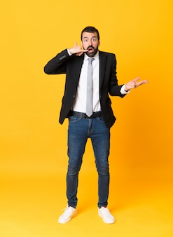 Full-length shot of business man over isolated yellow  making phone gesture and doubting