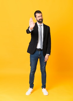 Full-length shot of business man over isolated yellow making stop gesture